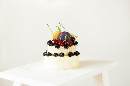 two floors: White small cake on two  floors decorated mulberry and  fresh cherry, two macaroons on top. Cake covers white  background. Stock Photo