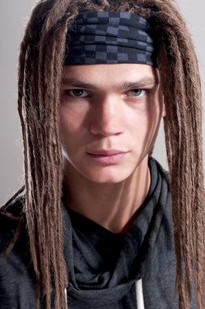 apathetic: Young stylish guy with dreadlocks.