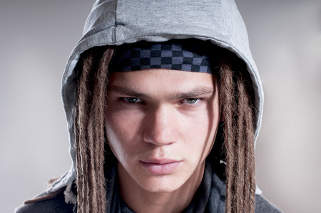 distrustful: Portrait of serious man with dreadlocks and wearing a hood over gray background.