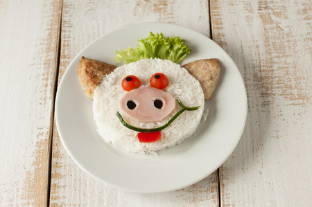 childrens meal: Cheerful pig from rice  and  cutlets on plate. Childrens meal.