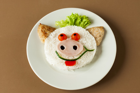 childrens meal: Cheerful pig from rice  and  cutlets. Childrens meal Stock Photo