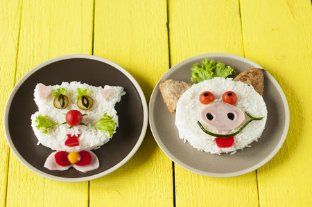 childrens meal: Cheerful pig and cat from rice  and  cutlets on plates. Childrens meal. Stock Photo