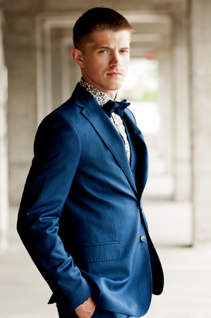 suit jacket: Handsome elegant man wears blue suit with bow tie outdoor.