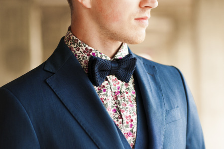 coat and tie: Dark blue bow tie with flowers shirt and suit on mens neck.