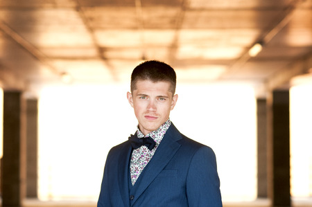 frontal portrait: Frontal portrait of a young attractive man in blue suit with bow tie. Stock Photo