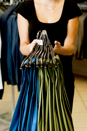 revision: Green and blue mens trousers on hangers in female hands. Revision in the store.