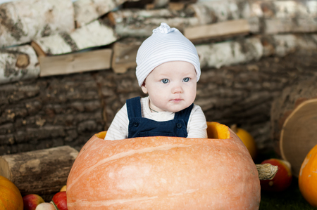 beautiful thanksgiving: Portrait of funny baby in big  pumpkin, over wooden background. Stock Photo