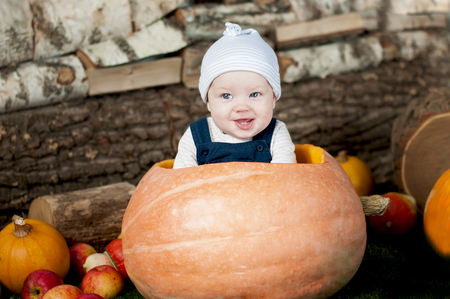 big and small: Portrait of funny baby in big  pumpkin, over wooden background. Stock Photo