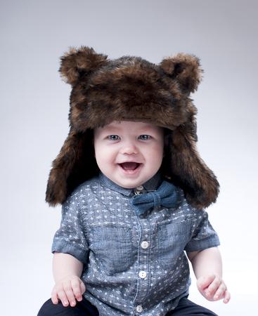 sombrero: Beb� divertido en un sombrero de piel del invierno cubre el fondo gris.