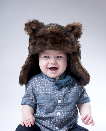 pretty baby: Funny baby boy in a winter fur hat cover gray background.