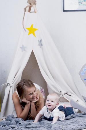 wigwam: Baby playing with her mother  on gray knitted carper near wigwam. Stock Photo