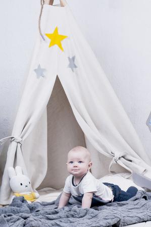 wigwam: Cute baby creeps on gray knitted carpet near wigwam.
