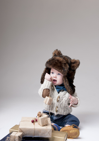 Funny baby in a winter fur hat with gift boxes over gray background. Stock Photo
