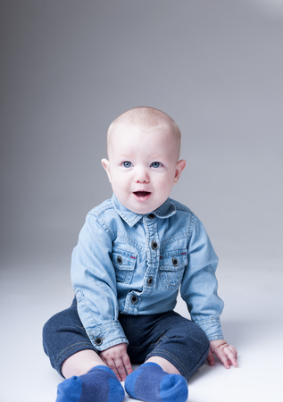 surprised baby: Surprised baby boy in denim shirt isolated on  gray background.