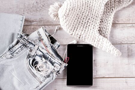 moder: Different objects fot moder young person.  Tablet, earphones, jeans, knitted hat folded on the wooden boards. Stock Photo