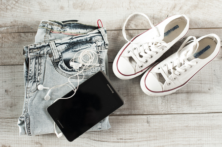 moder: Different objects fot moder young person. Tablet, earphones, jeans, gumshoes lie on the wooden boards. Stock Photo