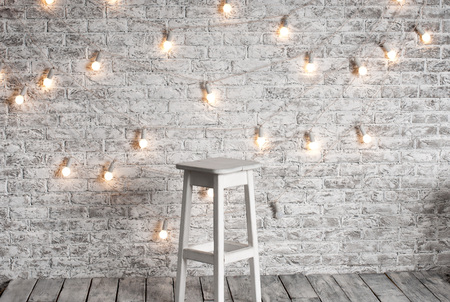 Blank white stool against the backdrop of a brick wall with a blank white stool against the backdrop of a brick wall with a garland of light bulbs aloadofball Gallery