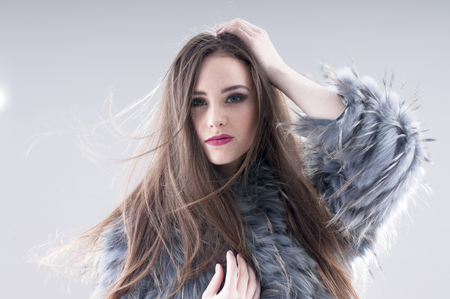 makeups: sensual girl in a gray coat over gray background