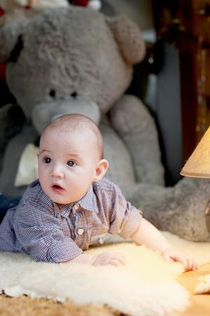 wonderment: Cute happy baby boy portrait lying on fur Stock Photo