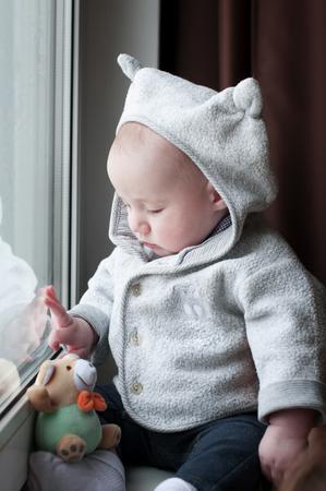 animal angelic: Cute happy baby boy  sitting near the window