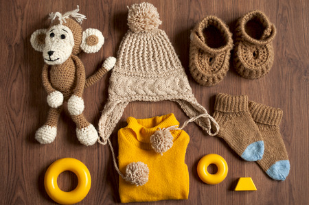 Flat lay.Baby knitted clothes and toys on a wooden background