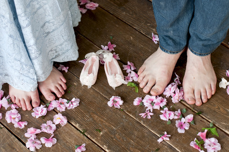 baby's feet: Family feet with babys bootees on wooden brown boards among flowers. Birth expectation concept. Stock Photo