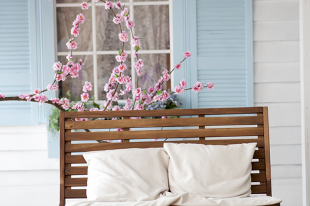 window bench: brown wooden bench with pillows for relaxing near the cherry blossoms in front of a window with blue shutters