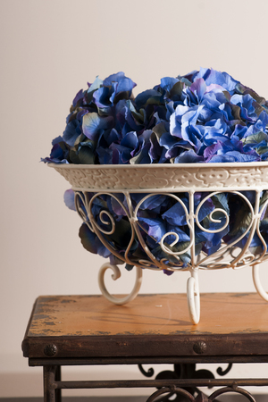 florid: flowers of blue hydrangeas in a metal florid forged  vase on  stools Stock Photo