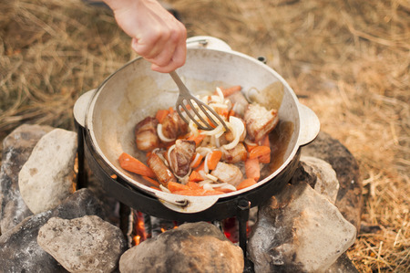 Shurpa -  cooking process on bonfire. Stock Photo