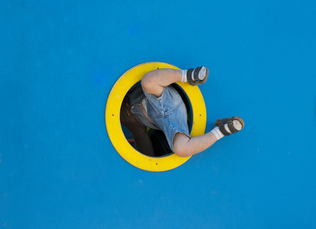 Funny kid playing in the playground.  a child tries to climb through the ships porthole. Stock Photo