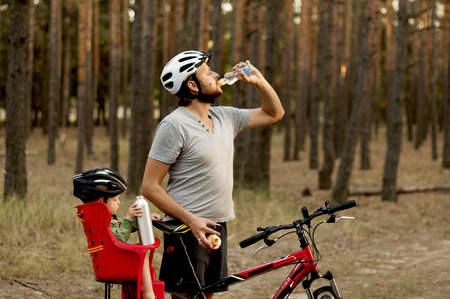thirst quenching: father and son on a bike ride in forest  took a break for quenching thirst Stock Photo