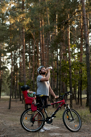 quenching: father and son on a bike ride in forest  took a break for quenching thirst Stock Photo