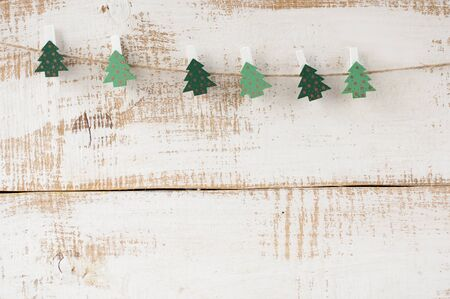 Wooden clothespins decorated Christmas trees hitched to the rope. Free space for text.