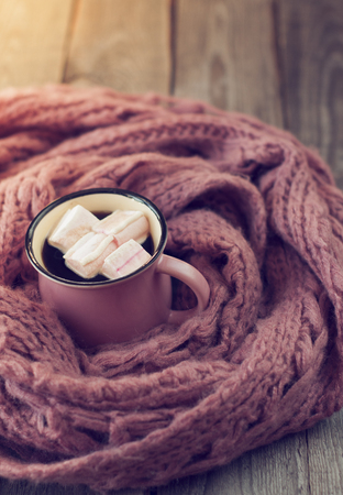 pink mug with a hot drink and marshmallow, wrapped in a pink scarf