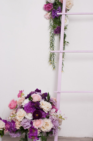 dangling: lush bouquet of roses in a flowerpot on the floor beside a decorative ladder