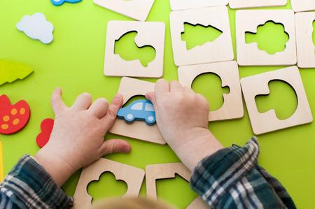 Mains d'enfants jouant avec un trieur de formes en bois à l'intérieur. Banque d'images