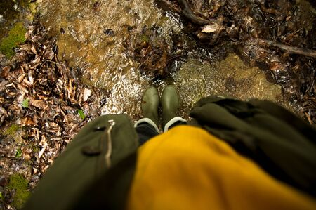 female feet in rubber boots standing in the shallow river