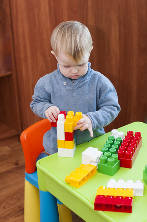 diligente: children spend time playing with constructor indoor.