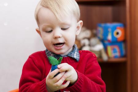 happy child holding a plum from plasticine indoor Stock Photo