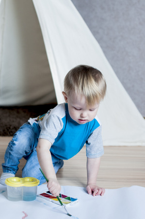 Concentrated kid draws a brush with watercolor paint behing the wigwam indoor Stock Photo