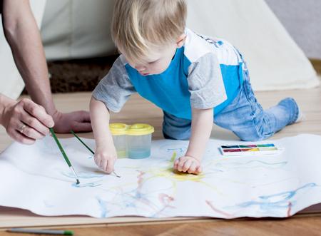 愛らしい小さな男の子が自宅で水彩絵の具でペイントしよう 写真素材 - 76403729