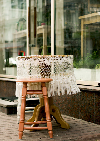 snugly: Street exterior. Small round table with white lace tablecloth near the showcase of a street cafe