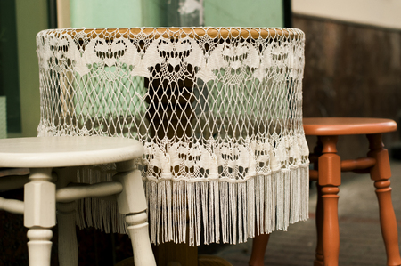 snugly: Lace tablecloth with fringe on the round table outdoos.