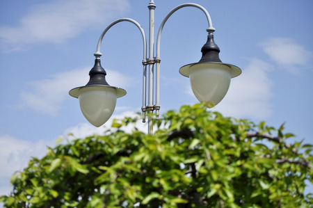 A lamppost in the garden against a blue sky background Stock Photo