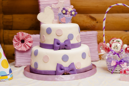 Two-tier cake made of mastic decorated with bows for one year Stock Photo