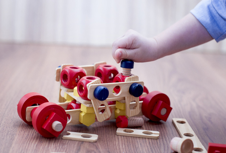 the child twists the bolt into a wooden machine made of eco constructor
