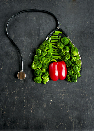 Imitation of healthy lungs and heart formed by broccoli and pepper with stethoscope, flat lay on dark background.