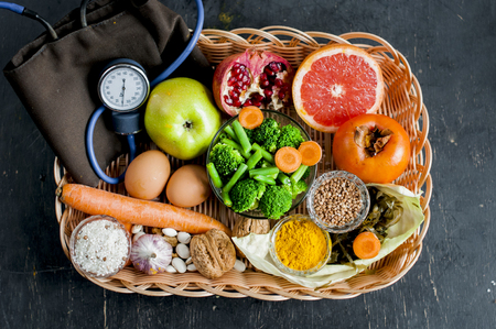a set of essential food products to maintain the vascular system in straw tray with a blood pressure tonometer  flat lay on dark background.