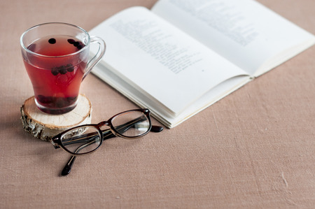 Blueberry tea in a clear glass cup on a round wooden stand with glasses and a open book on a brown tablecloth. Stock Photo