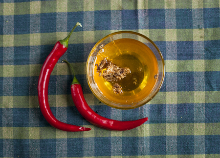 liquid honey with honeycombs in a glass bowl with  chilli paper on  tableclothes